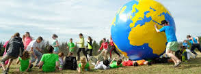 Several students play with a gigantic inflatable GLOBE.