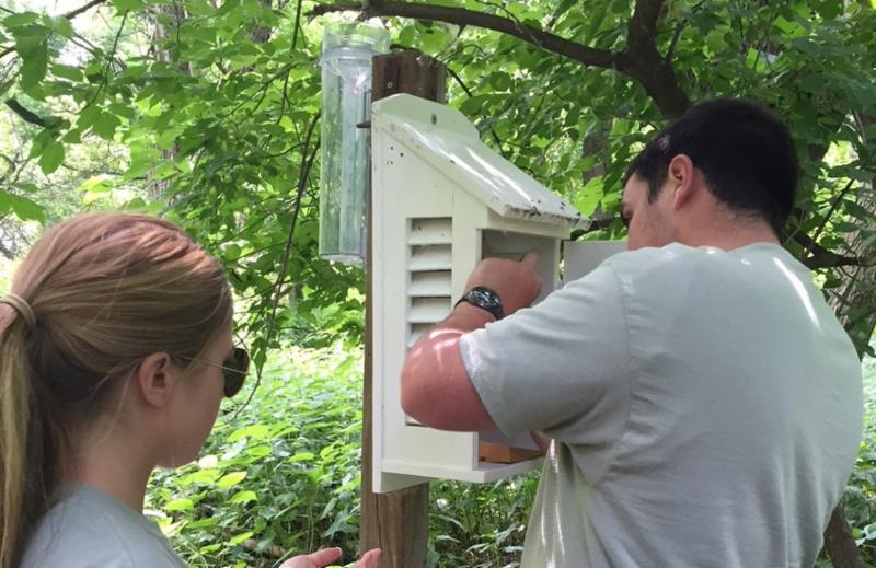 Two adult with their backs facing us gather data from a weather station.
