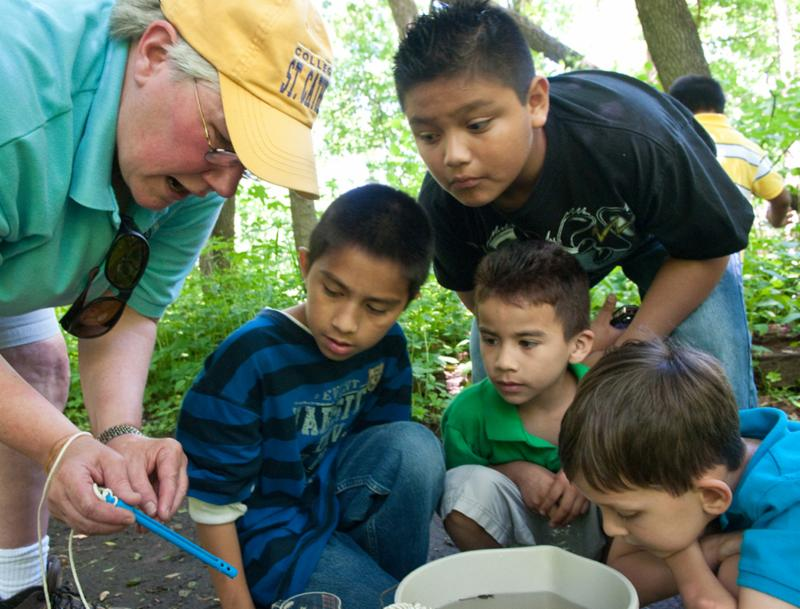 A teacher works with several students outdoors.
