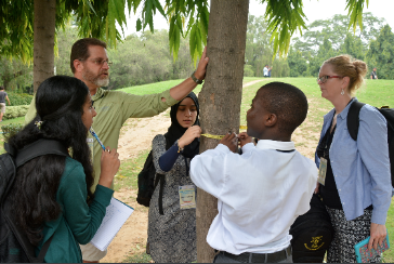 Teachers and students gather around a tree.