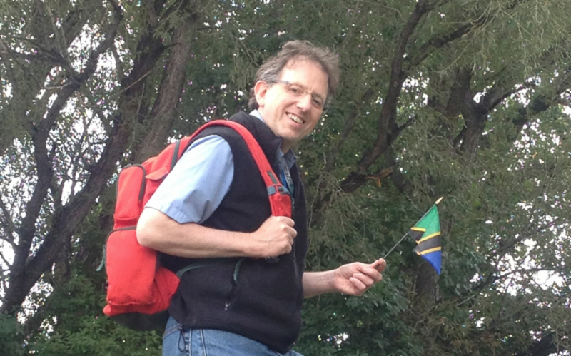 A man is seen carring a rucksack and a flag of Tanzania, Africa.