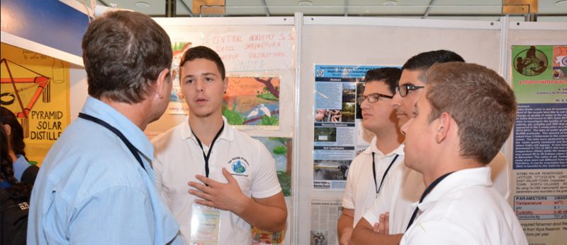 A young adult student explains his poster to a scientist while other students look on.