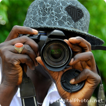 A boy holds a camera with a large lens up to his face.
