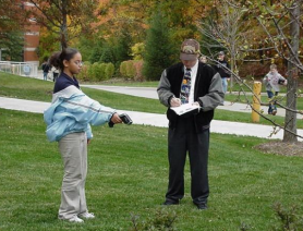 A student works with a teacher to take a measurement in a field.