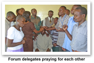 Forum delegates praying for each other
