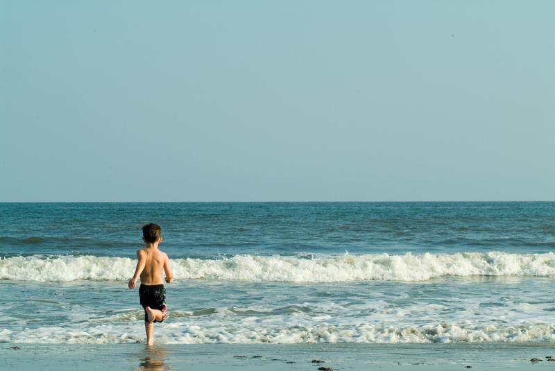 Young boy running into the ocean.