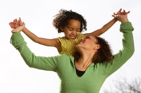 Mother, daughter with arms spread