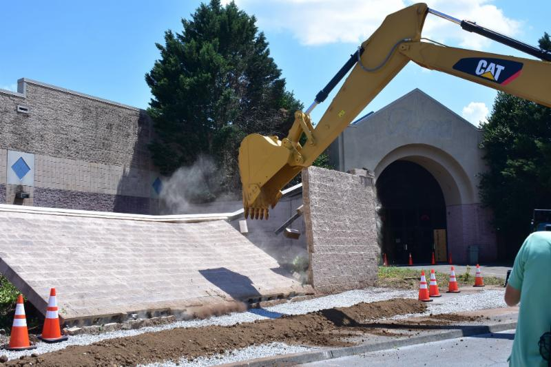 City Councilman Chuck Hope uses excavator to knock down wall