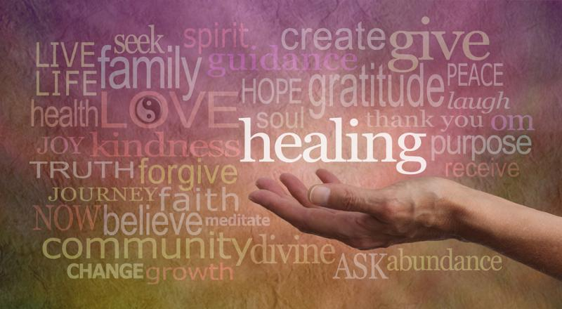 Healer s outstretched open hand surrounded by random wise healing words on a rustic stone effect background