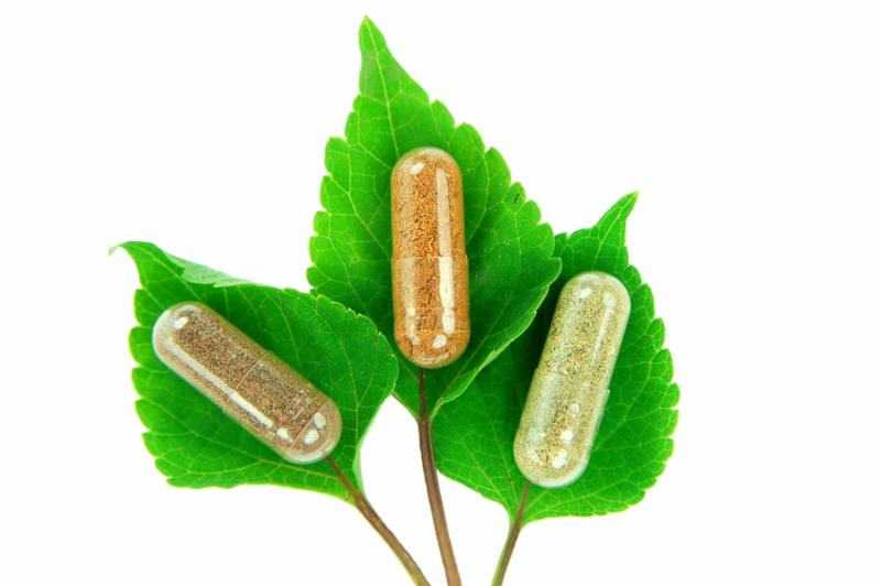 herbal capsules on sage leaves on white background