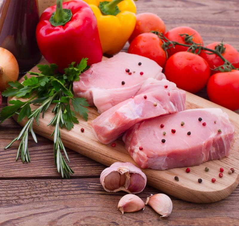 Food. Sliced   pieces of raw meat for barbecue with fresh vegetables and mushrooms on wooden surface. Meat raw steak. Beef steak bbq. Tomatoes, peppers, spices for cooking meat.