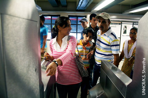 Refugee family navigating American subway system. Photo courtesy of UNHCR/K.S. Shrestha.