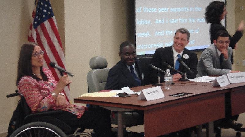 Smiling people sit at a panel table with a sign language interpreter in the background.