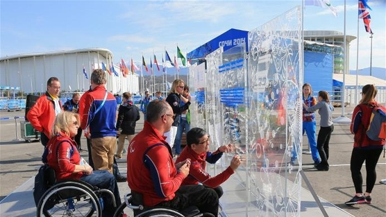 Aeveral people, some in wheelchairs, are seen writing on a clear wall surrounded by National flags ourtside