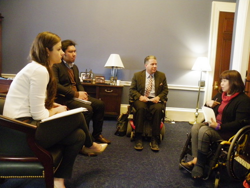 Two people in wheelchairs and two in chairs participate in a lively discussion.