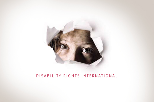 White sheet of paper with a torn hole showing a neglected child_s dirty face Below face it says Disability Rights International