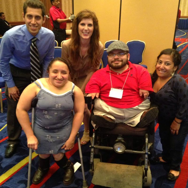 Three little people, one in a wheelchair and one on crutches, smile at the camera while a man and a woman stoop down in the back row to get in the picture.