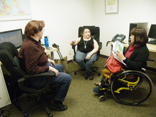 Two people in chairs and a woman in a wheelchair face each other while they are having an animated discussion.