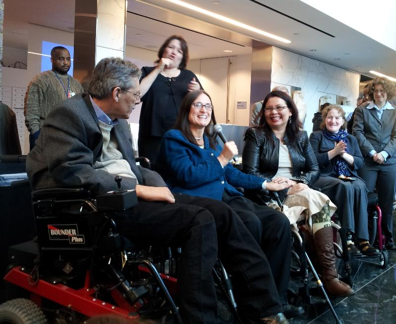 Four people in wheelchairs sit addressing a room of people with an ASL intepreter behind them.