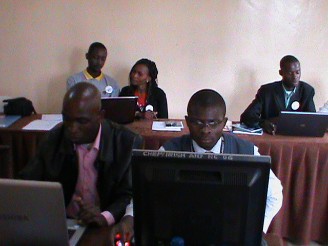 Several Africans crowd arounf three different computers in deep study.