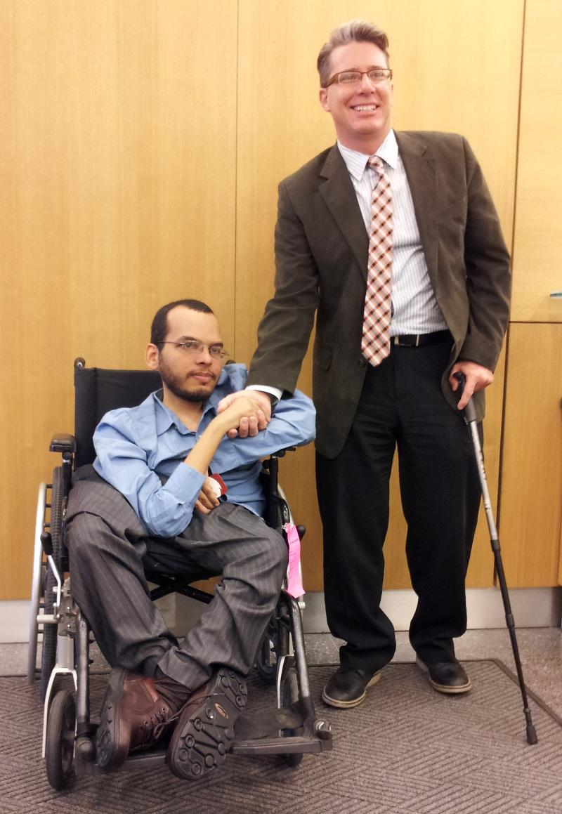 A gentleman standing with a cane faces the camera while shaking the hand of a gentleman in a wheelchair.