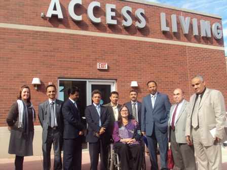 A group of people stand outside in front of a brick building that says Access Living