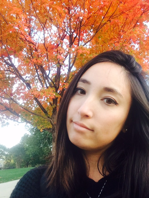 Rebecca Yim looks at camera. A tree with autumn orange leaves is behind her.