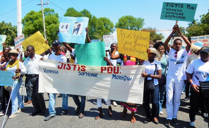 A large group of people march with signs in French and a large banner with the names Vanessa Sophonie Monique