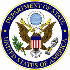 A blue circle that says Depart of State the United States of America surrounding an eacgle with a shield clutching a branch and some arrows