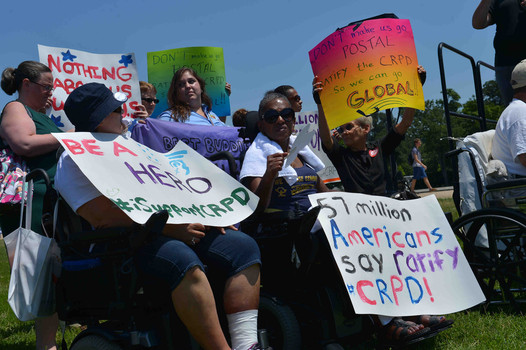 People of all colors and disabilities hold signd supporting the CRPD under a clear blue sky