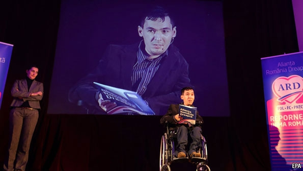 Romanian candidate in wheelchair reads from a book on  a stage with a larger picture of himself projected behind him