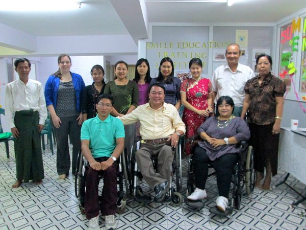 Group of people with row of nine standing people in back three wheelchair users in front