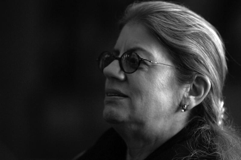 The black and white profile of a woman with light hair and dark glasses.