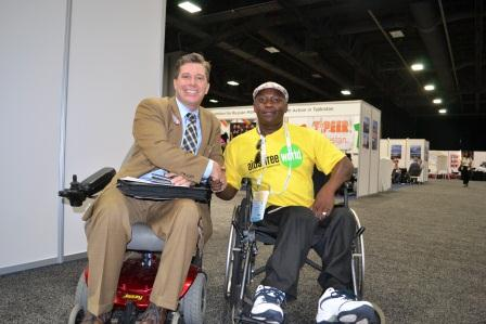 Two gentlemen in wheelchairs shake hands.  One is white in a suit and the other is black wearing a t-shirt and jaunty hat