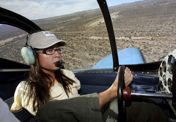 A young woman in a baseball cap and headphones is seen in the cockpit of an aircraft in flight steering with her foot.