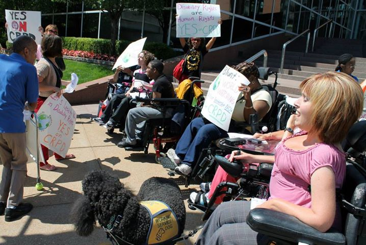 A row of people in wheelchairs as well as some on crutches and service animals form a line in front of a flight of steps holding signs supporting the CRPD