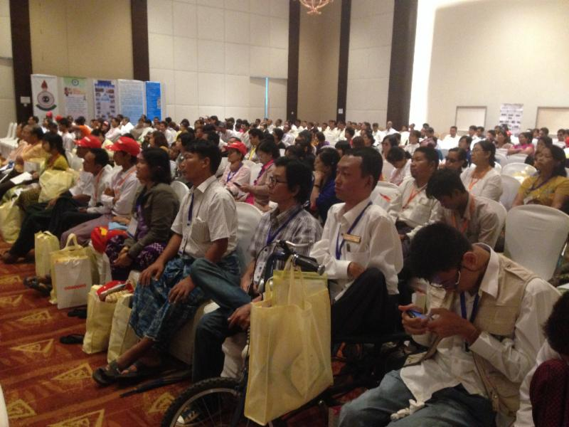 Hundreds of people seated in rows, waiting for the first National Disability Convention in Myanmar to begin