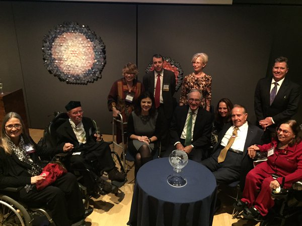 Key disability leaders in suits and other formal wear seated or standing around a cocktail table at USICD_s 2015 Annual Gala event