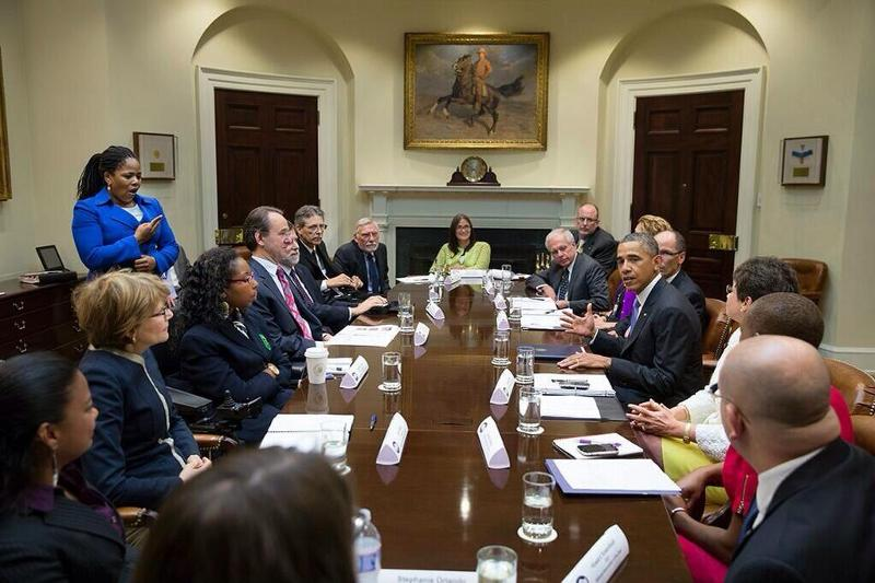 A group of disability advocates sit around a conference table talking actively with President Barack Obama