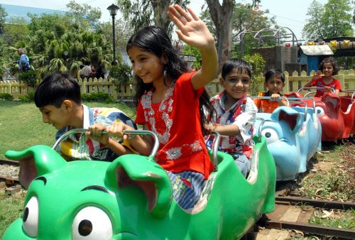 Several Indian children sit and play in a brightly colored train-like outdoor recreation equipment