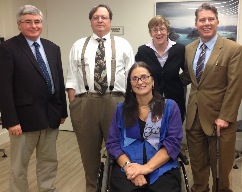 Two women and three men in business attire, one of the women in a wheelchair, smile at the camera