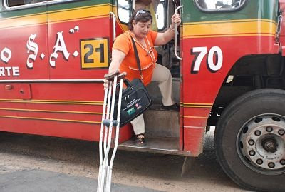 Person with crutches struggles to get on a bus.