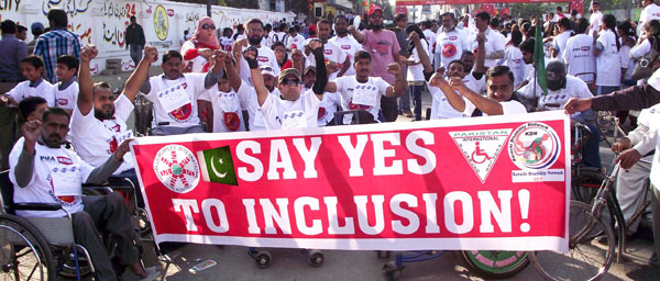 A large group of people, some in wheelchairs, cluster around a large red banner that says