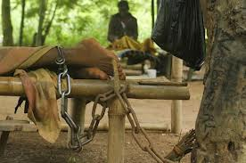 A person's foot chained to a table.