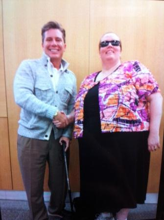 A gentlman wearing a suit shir and pants shakes hands with a woman wearing a floral shirt over a black dress and dark sunglasses