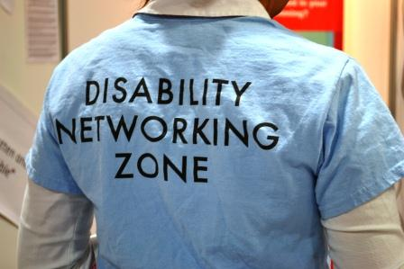 We see the back of someone from the neck to the waise wearing a light blue shirt that says Disability Networking Zone