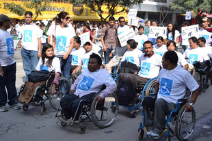 A group of young people, all wearing ,matching white tee shirts and holding signs, come of them in wheelchairs.