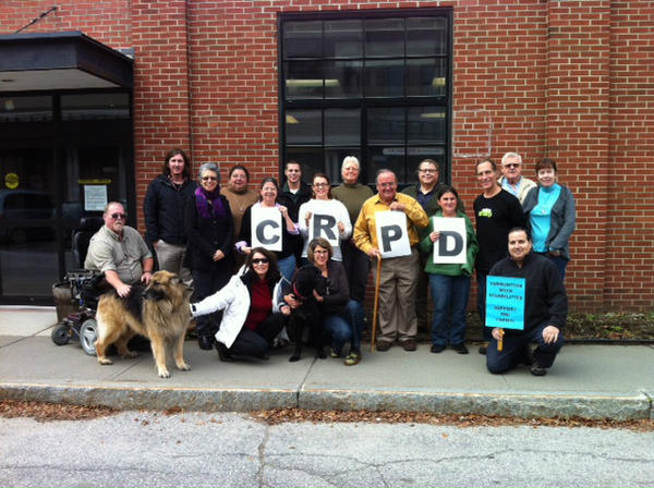 A group of peopleincluding an man in a wheelchair and a service dog pose together outside a red brick building holdingthe letters CRPD