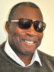 A man wearing sweater and dark sunglasses smiles at the camera