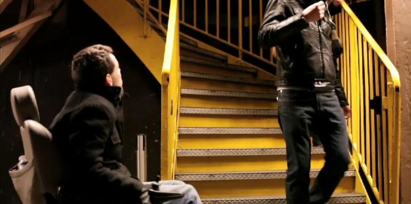A man in a wheelchair looks up a yellow set of metal stairs as somene walks down them.